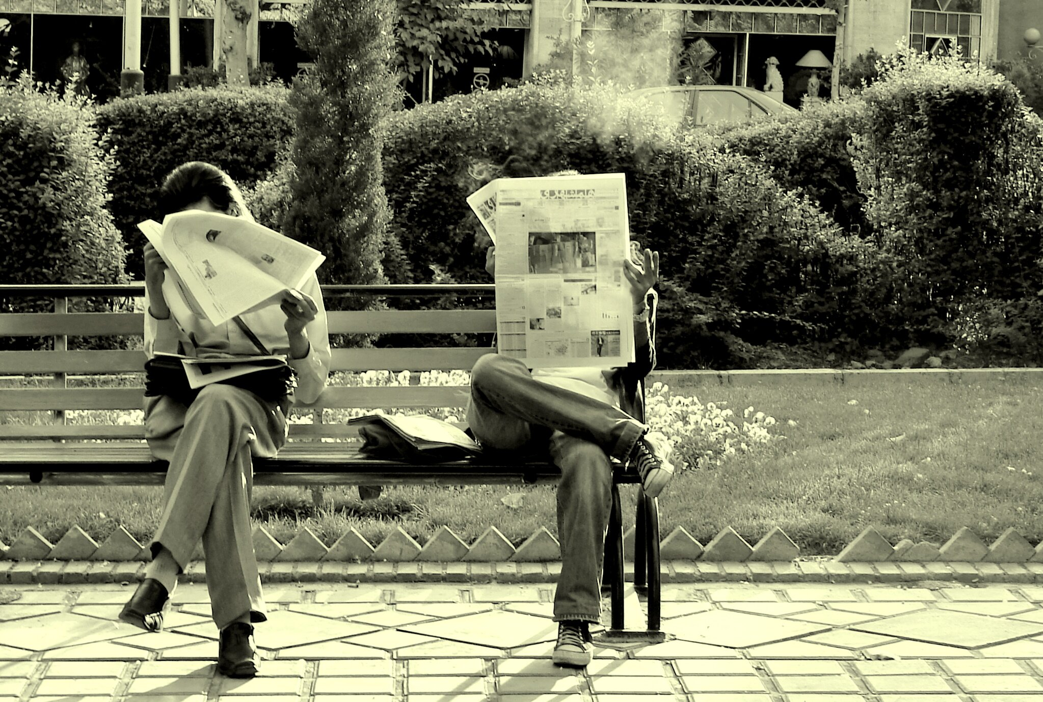 Two men sitting on a park bench and reading the newspaper